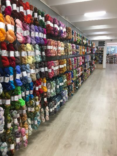 View of the wall of the shop full of hand-dyed yarn skeins