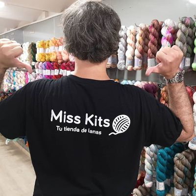 A boy with a t-shirt with Miss Kits logo and the tagline Your yarn shop, in Spanish