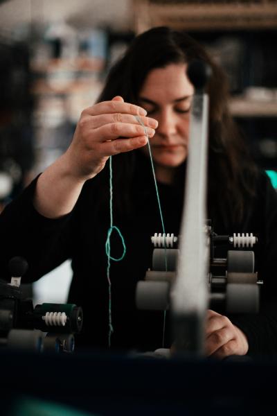 Jess spinning yarn at Olann Mills